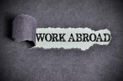 Work abroad word under torn black sugar paper Stock Photos