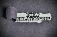 built relationship word under torn black sugar paper - stock photo