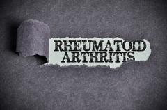 Rheumatoid arthritis word under torn black sugar paper Stock Photos