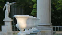 Flower pot marble sculptures and a man statue in Lazienki Park, Warsaw Stock Footage