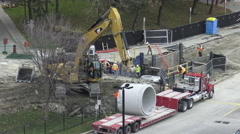 Excavator Carrying Cement Pipe Stock Footage