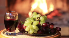 Plate with grapes and glass of wine on fireplace background Stock Footage
