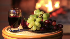 Plate with grapes and glass of wine on fireplace background - stock footage