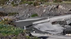 Van negotiates a ford on Cape Palliser road, N.Z. Stock Footage
