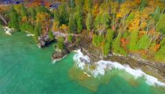 Emerald waves crash on rocky Autumn shores. - stock footage