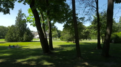 Lying on grass, walking and playing badminton in Lazienki Park, Warsaw Stock Footage