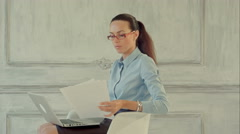Attractive businesswoman reading stats and graphs on paperwork Stock Footage