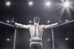 mma fighter in arena celebrating win, behind view - stock photo
