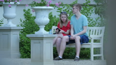 Couple resting on a bench at Lazienki Park, Warsaw Stock Footage