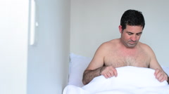 Upset man in bed looking down at his penis Stock Footage