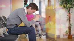 4K Worried man sits alone in hospital waiting area  - stock footage