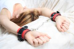 Female hands in leather handcuffs. on the background sheet. sex toys Stock Photos