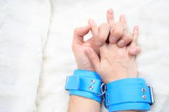 Male and female hands in handcuffs. sex Toys - stock photo