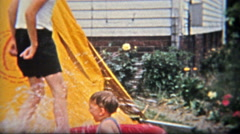 1954: Brother splashing baby boy in kiddie backyard fun pool. Stock Footage
