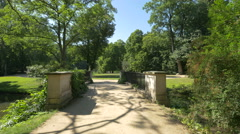 Bridge over a river and two empty benches in Lazienki Park, Warsaw Stock Footage