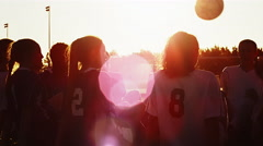 A soccer team sitting in a circle playing a fun game at sunset Stock Footage