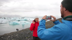 Couple taking photo with smartphone by Jokulsarlon Iceland Stock Footage