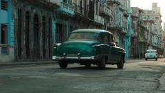 Colorful buildings and classic cars driving on an old Havana street - stock footage