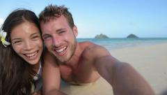 Couple relaxing on beach taking selfie picture - happy people having fun - stock footage