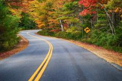 Winding road through autumn trees in New England - stock photo