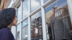 4K Woman looking in window of a man's clothing store. - stock footage