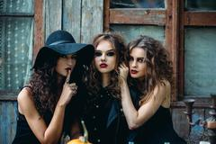 Three vintage witch sitting at the table Stock Photos