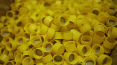 Many yellow plastic bottle caps, close-up. Stock Footage