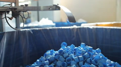 Many blue plastic bottle caps fall from conveyor to the box. Stock Footage