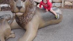 Boy on statue lion in the zoo Stock Footage