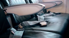 Seat belts lie on seats in the old plane economy class Stock Footage