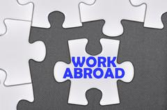 Jigsaw puzzle written word work abroad Stock Photos