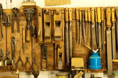 assortment of do it yourself tools hanging in a wooden cupboard against a wal - stock photo