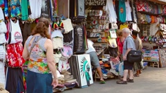 Tourists shopping at souvenir stalls in the town of Kuta, on the island of Bali Stock Footage