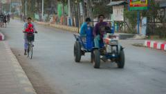 Bicycles, motorcycles and a tractor, rolling down a city street in Myanmar Stock Footage