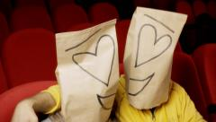 Breadbags faces movie theater lovers Stock Footage