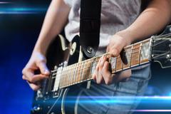 musician playing electric guitar with mediator - stock photo