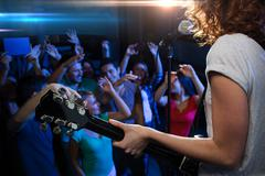 female singer playing guitar over happy fans crowd - stock photo