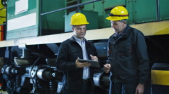 Two Technicians in Hard Hats Have Conversation next to Train. Stock Footage