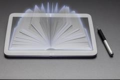 Tablet pc with a book hologram - stock photo