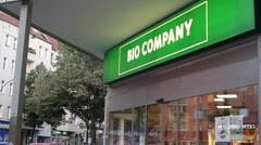 Man exits organic supermarket shop, Bio Company, Berlin, Germany Stock Footage