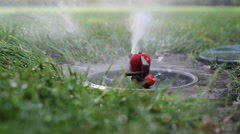 Mechanical water sprinkler waters the grass in the park, close up, shallow DOF Stock Footage
