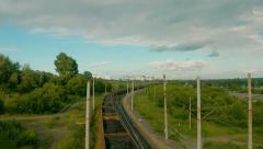 Timelapse clouds over the green field and rail road Stock Footage