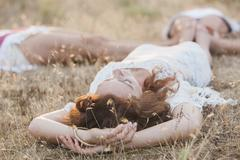 Boho women laying in circle with feet touching in rural field - stock photo