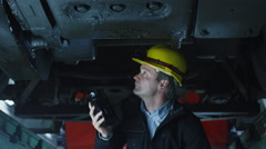 Technician in Hard Hat with Flashlight in Hand Inspecting Train - stock footage