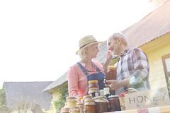 Affectionate senior couple selling honey at farmer's market Stock Photos