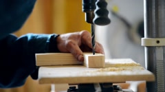 The man on the joiner's machine saws a wooden board Stock Footage