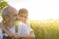 Portrait affectionate grandson hugging grandfather in rural wheat field Stock Photos