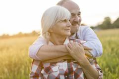 Stock Photo of Senior couple hugging in rural wheat field