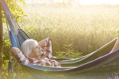Serene senior woman laying in hammock next to rural wheat field - stock photo