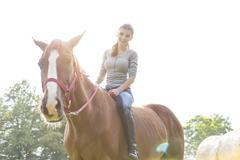 Smiling woman riding horse bareback Stock Photos
